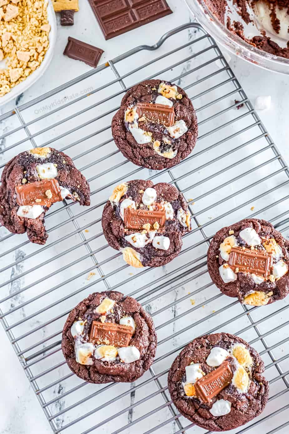 Chocolate S'mores cookies cooling on a rack, one has a bite missing.