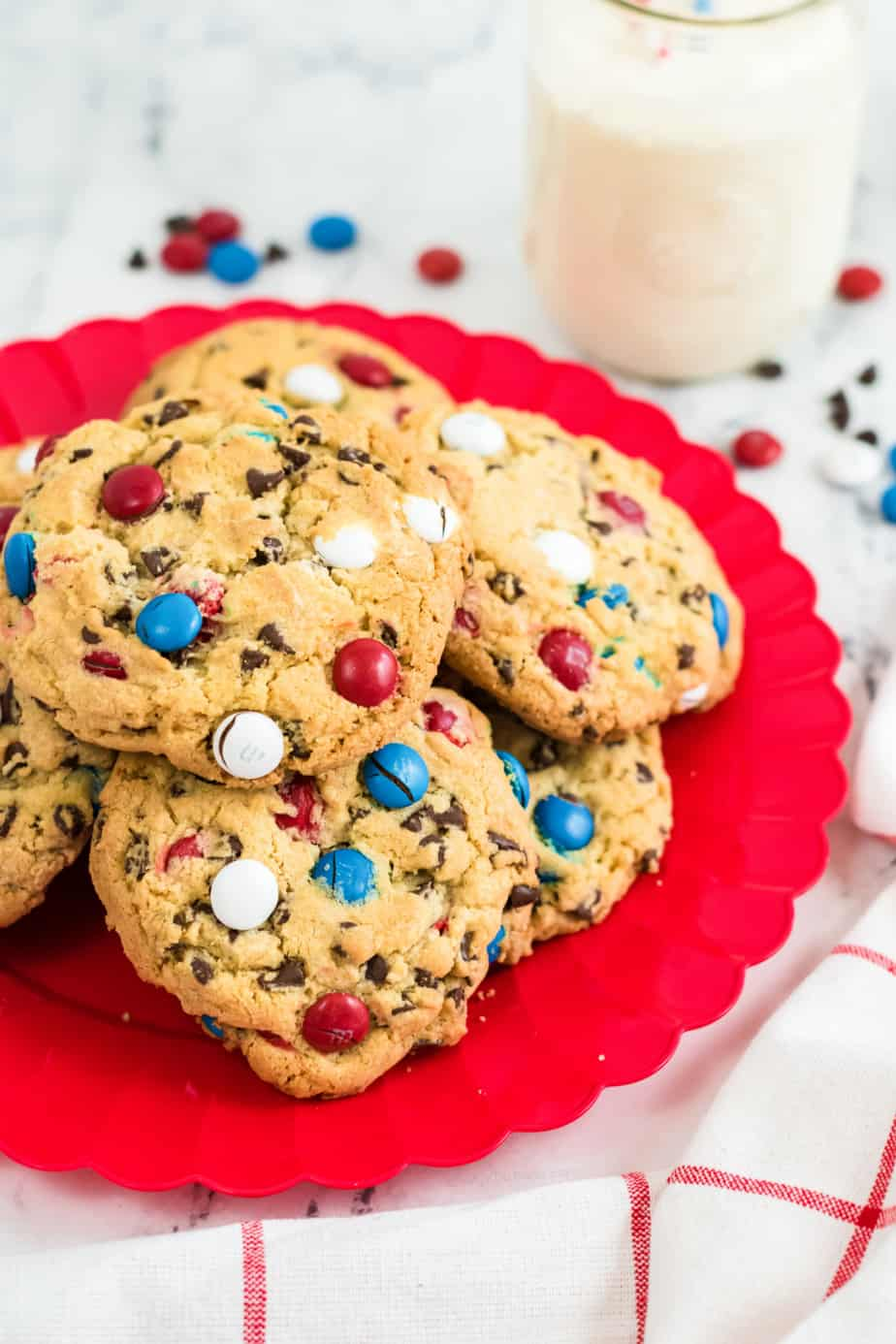 Cookies on a platter with red, white and blue M&M candies and milk in the background