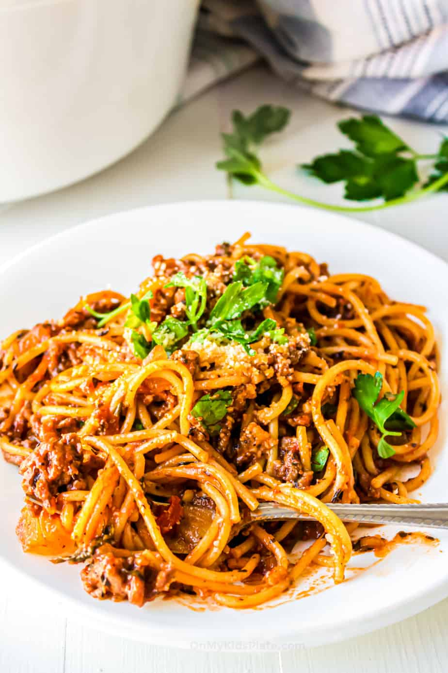 Spaghetti in a red sauce with ground turkey on a plate with a fork.