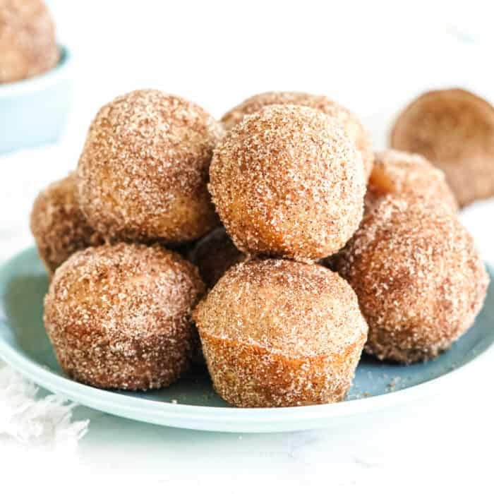 A stack of doughnut holes covered in cinnamon sugar on a plate from the side