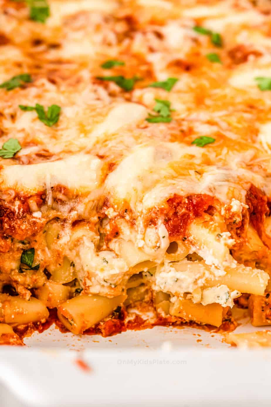 Close up of baked ziti with ricotta, tomato sauce and gooey mozzarella cheese on top.