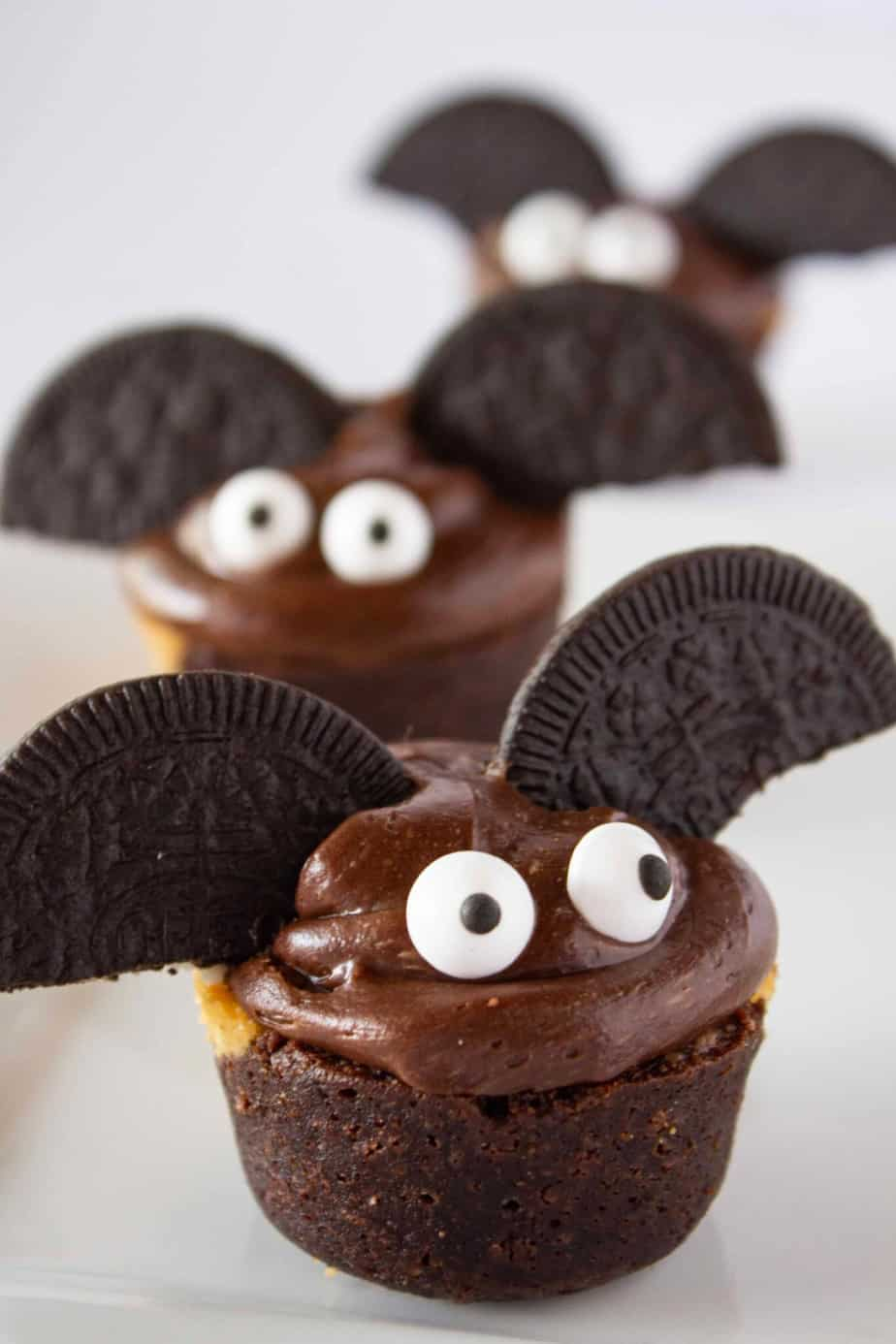 Brownie bite decorated to look like a bat with frosting and Oreo cookies