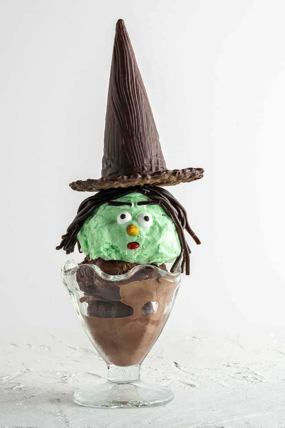 Ice cream sundae decorated like a witch with a green face from the side