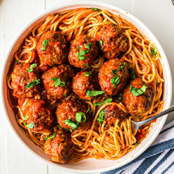 Meatballs in pasta sauce over top of spaghetti in a bowl