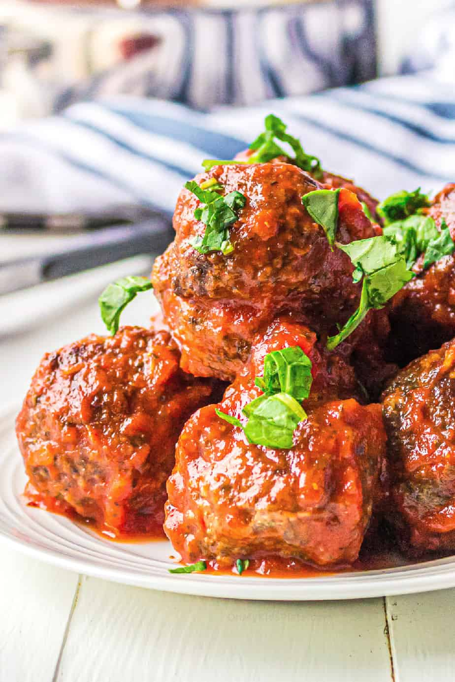 Beef meatballs in red pasta sauce stacked high from the side close up with parsley sprinkled on top.