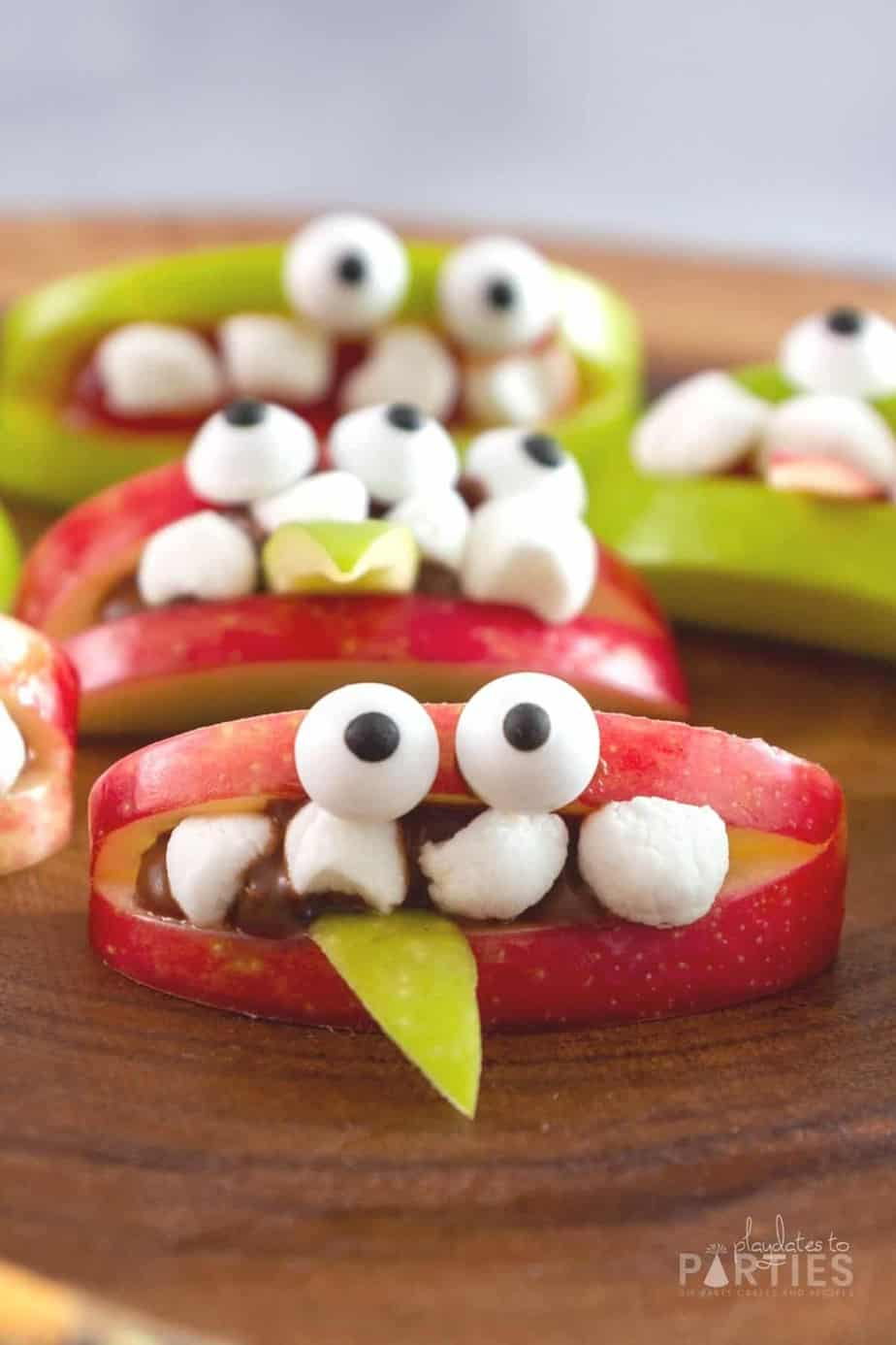 Apple slices decorated with marshmallows and candy eyes to make a monster face