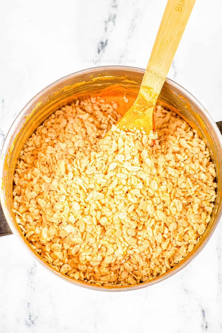 Adding Rice Krispie cereal to a pan on top of the pumpkin mixture.
