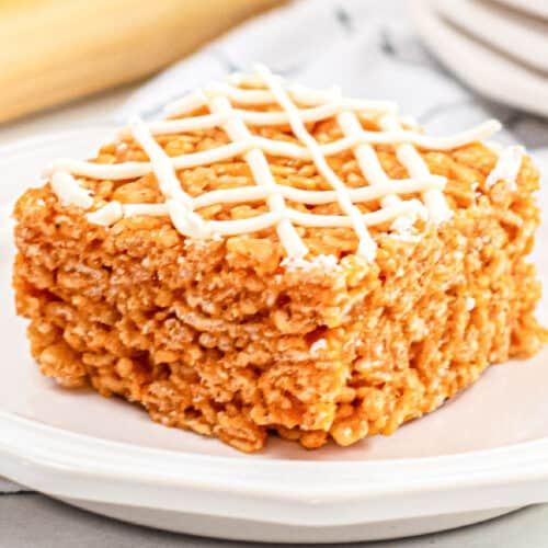 Orange pumpkin rice krispie treat at an angle on a plate close up topped with white chocolate