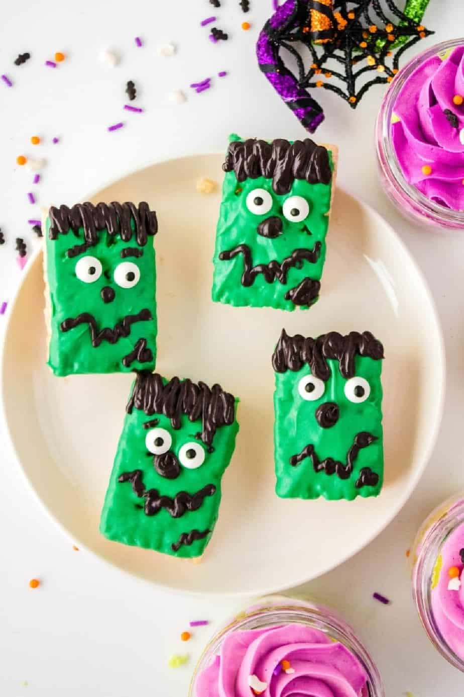 Rectangle rice krispie treats decorated like green Frankenstein monsters on a plate.