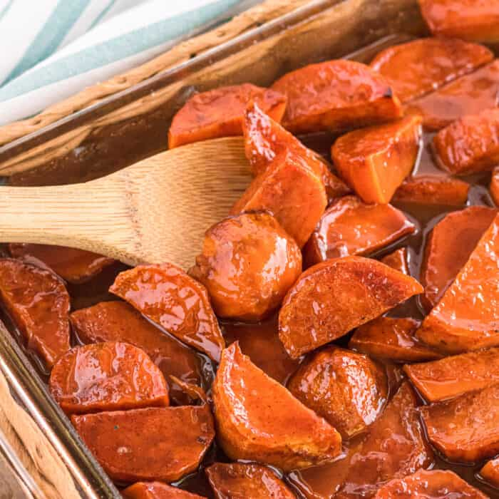Close up candied yams in a pan with a wooden spoon scooping