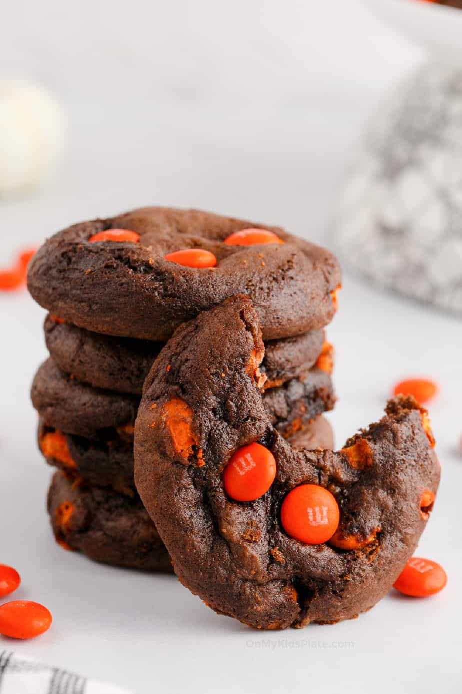 Stack of chocolate cookies with orange candies. One cookie has a bite missing