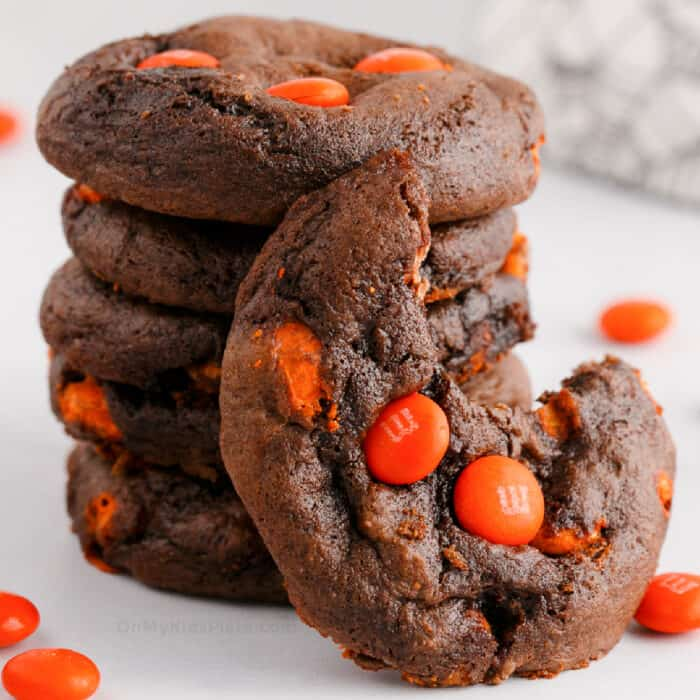 stack of chocolate cookies with orange candies, one cookie has a bite missing