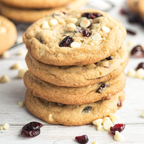 Close side view of four cranberry white chocolate cookies stacked with more cookies and extra chocolate and cranberries scattered nearby.