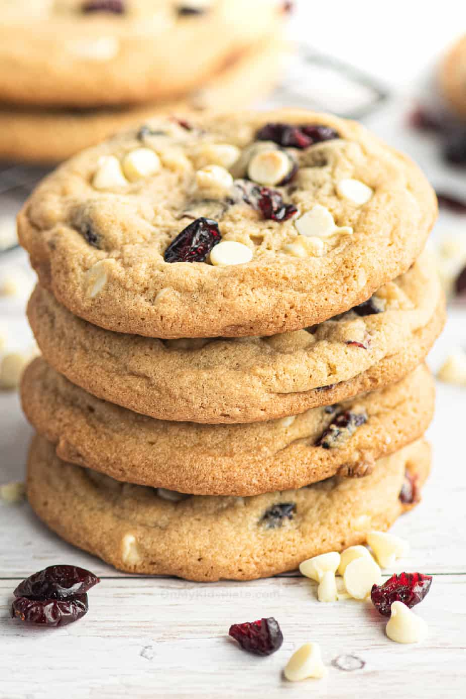 Super close up of four stacked white chocolate chip cranberry cookies from the side