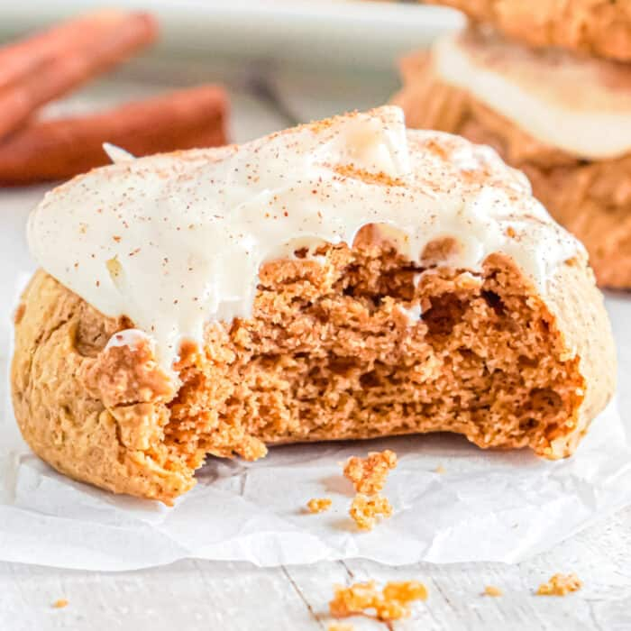 Up close view of a pumpkin cookie with frosting with a bite missing