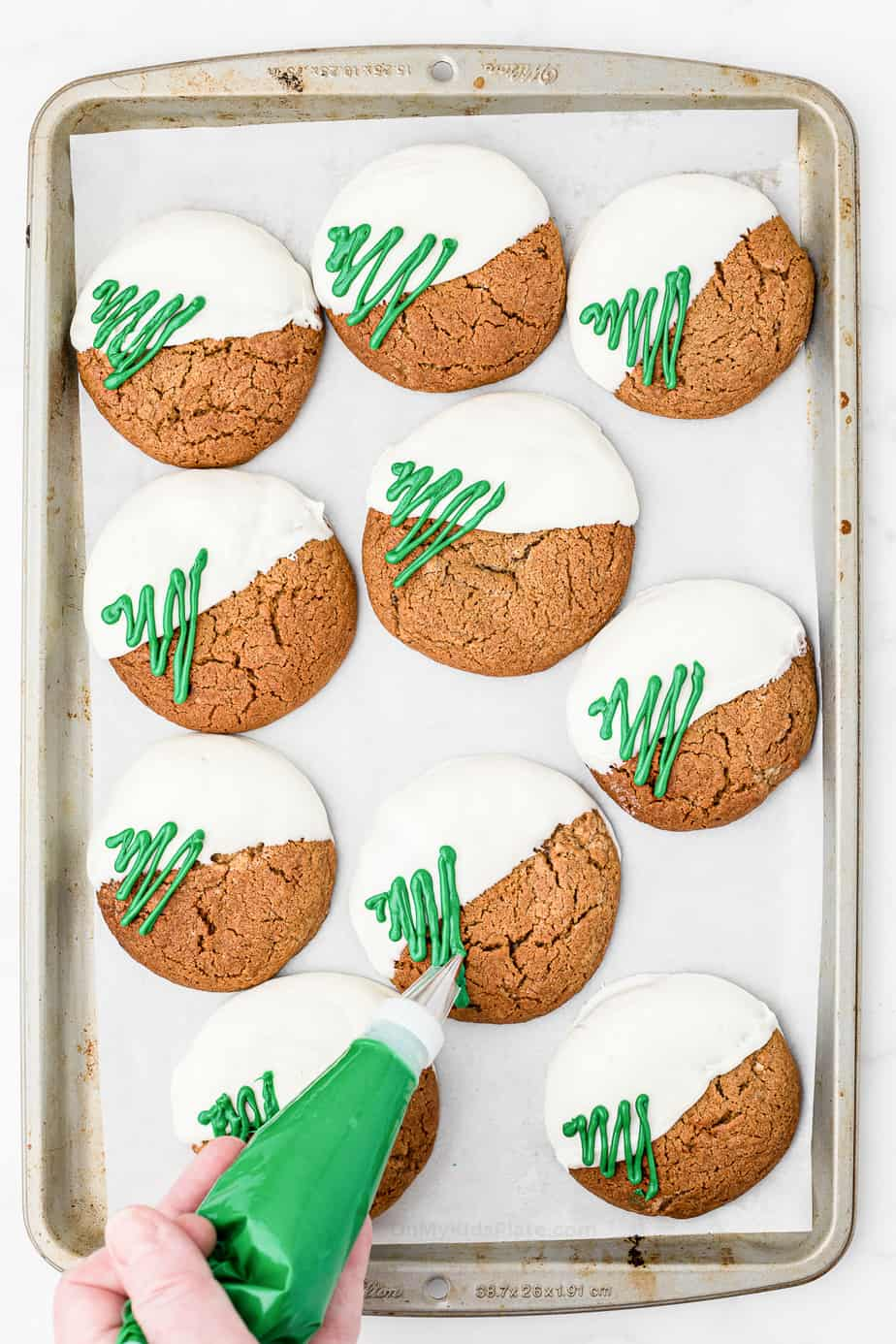 Molasses cookies dipped in white chocolate on a pan with green squiggle chocolate Christmas trees being added with a piping bag.