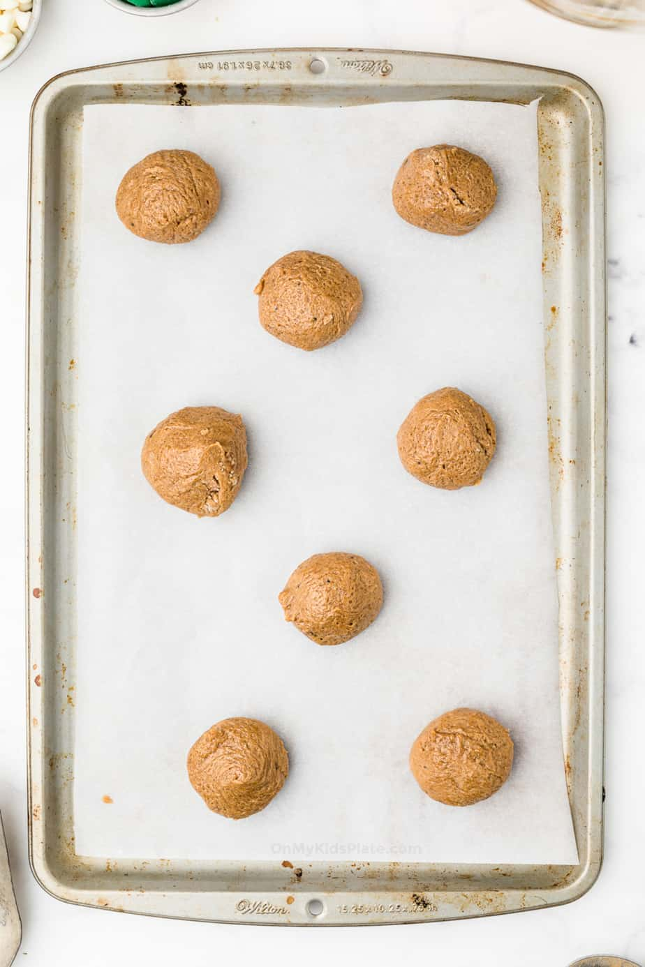 Molasses cookie dough on a cookie sheet lined with parchment paper