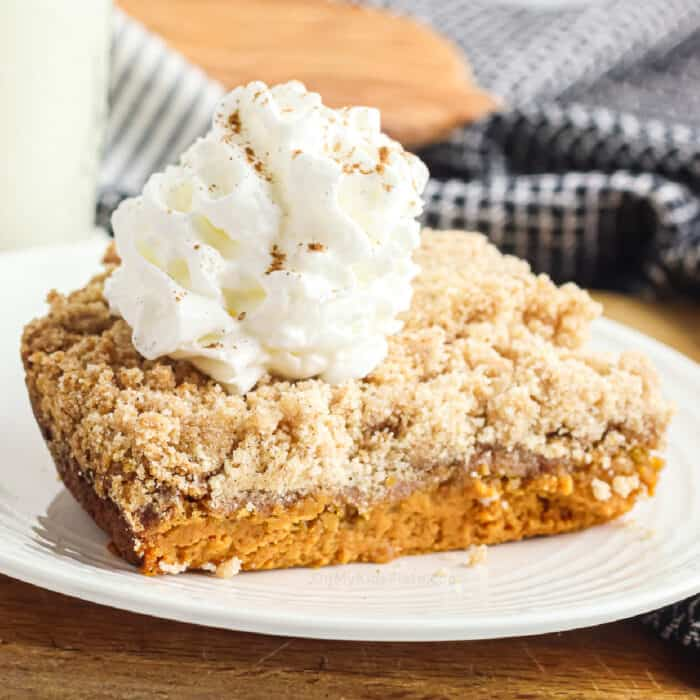 Up close layered pumpkin dump cake topped with whipped cream from the side