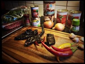 Ingrediënten voor chilli con carne op een snijplanp. Gerookte pepers, bonen, kruiden