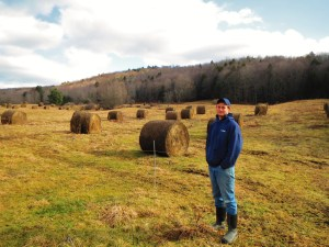 Tom McGrath poses with his checkerboard of round bales which he uses to direct feed his organic dairy cows in the winter.