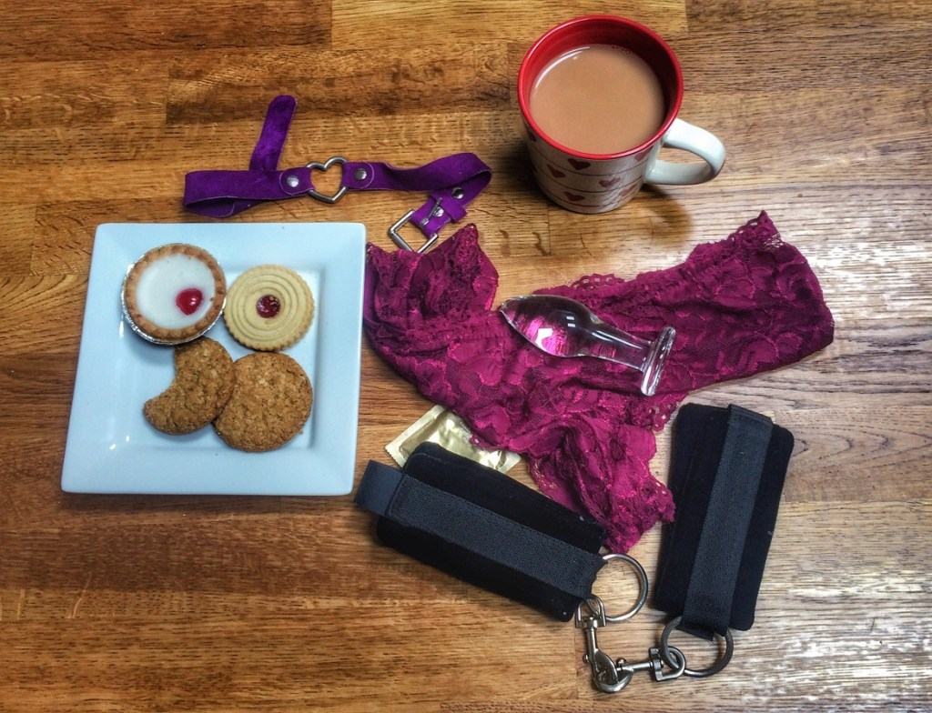 A plate of biscuits, a cup of tea, pretty knickers, a butt plug, condoms, cuffs and a collar, all arranged on a wooden floor.