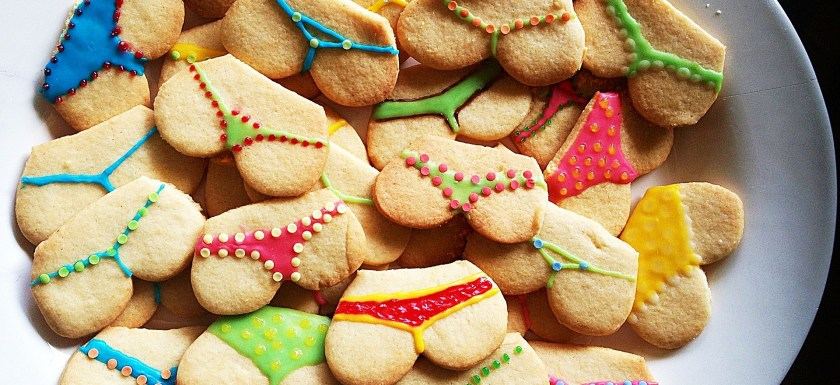 A plate of cookies in the shape of butts, with fancy icing knickers piped on to them.