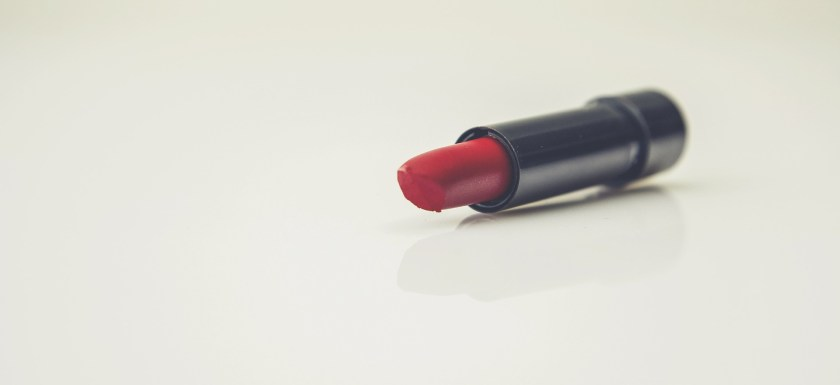 A red lipstick lies on a table. Photo.