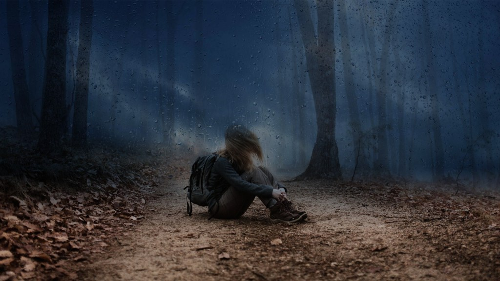 Image of a girl in hiking gear, including boots and a backpack, sitting down in the rain.