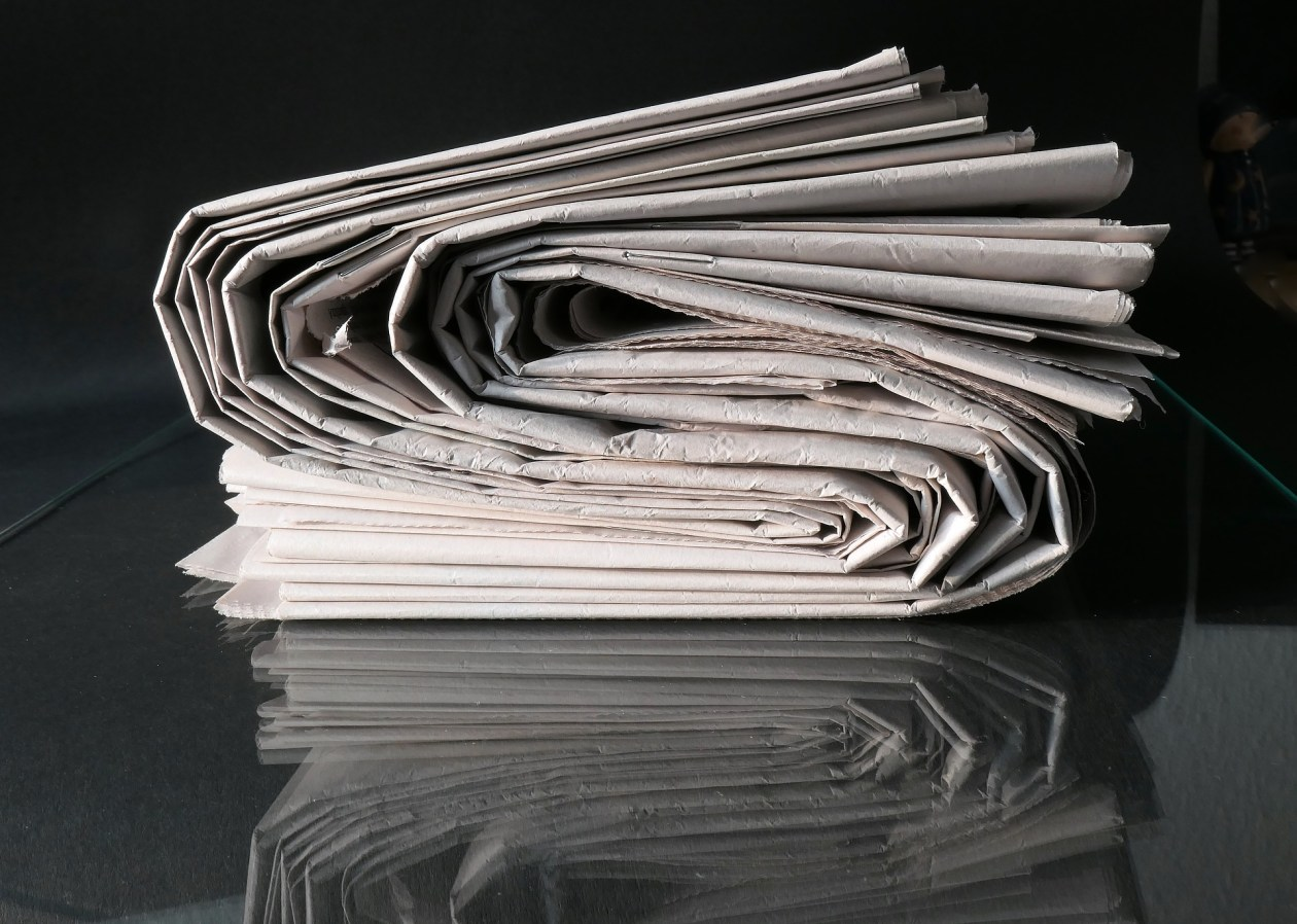 A wad of folded up newspapers placed on a reflective black surface that mirrors them in its shine.