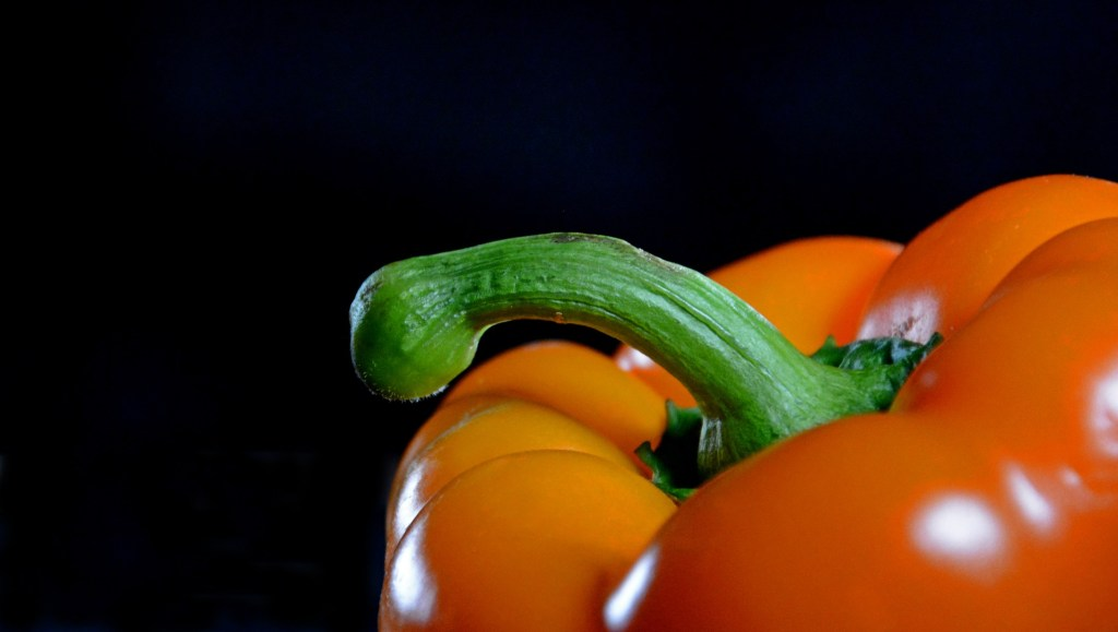 Photo of an orange sweet pepper, with a prominent green stalk that puts in mind a certain piece of anatomy.