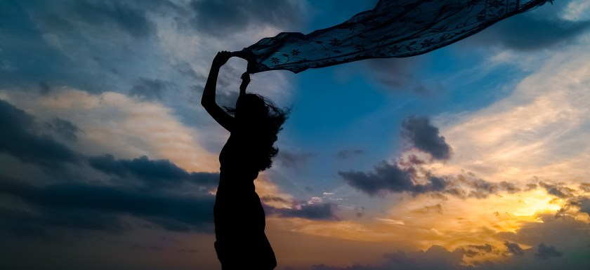 Silhouette of a woman against a blue skin with clouds and pink-gold sunset, holding a scarf above her head that's blowing backwards in the wind.