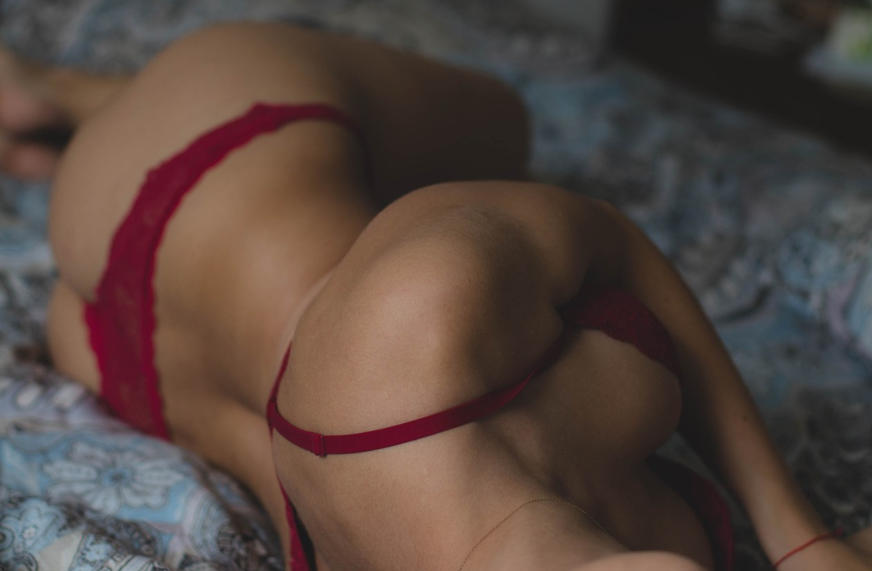 Woman lying with her back to the camera in a red bra. Photo.