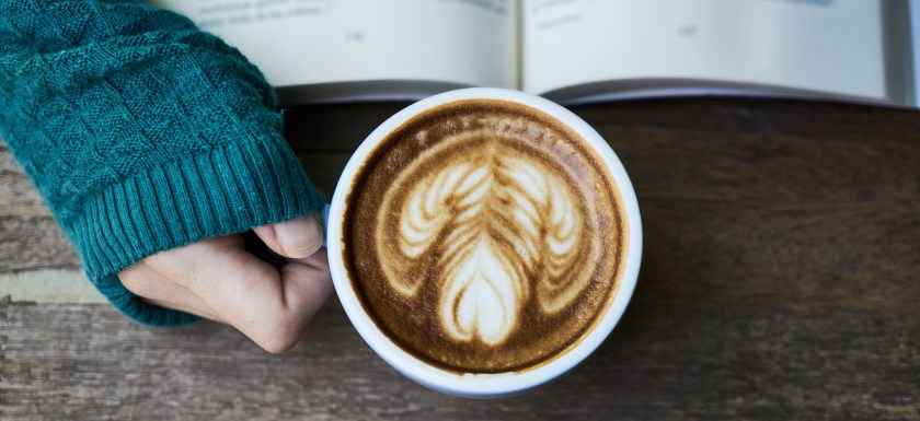 A coffee cup and an open book on a table. Photo.