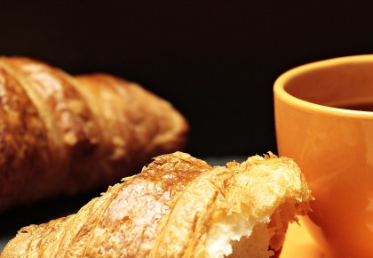 Coffee cups and chocolate croissants. Photo.