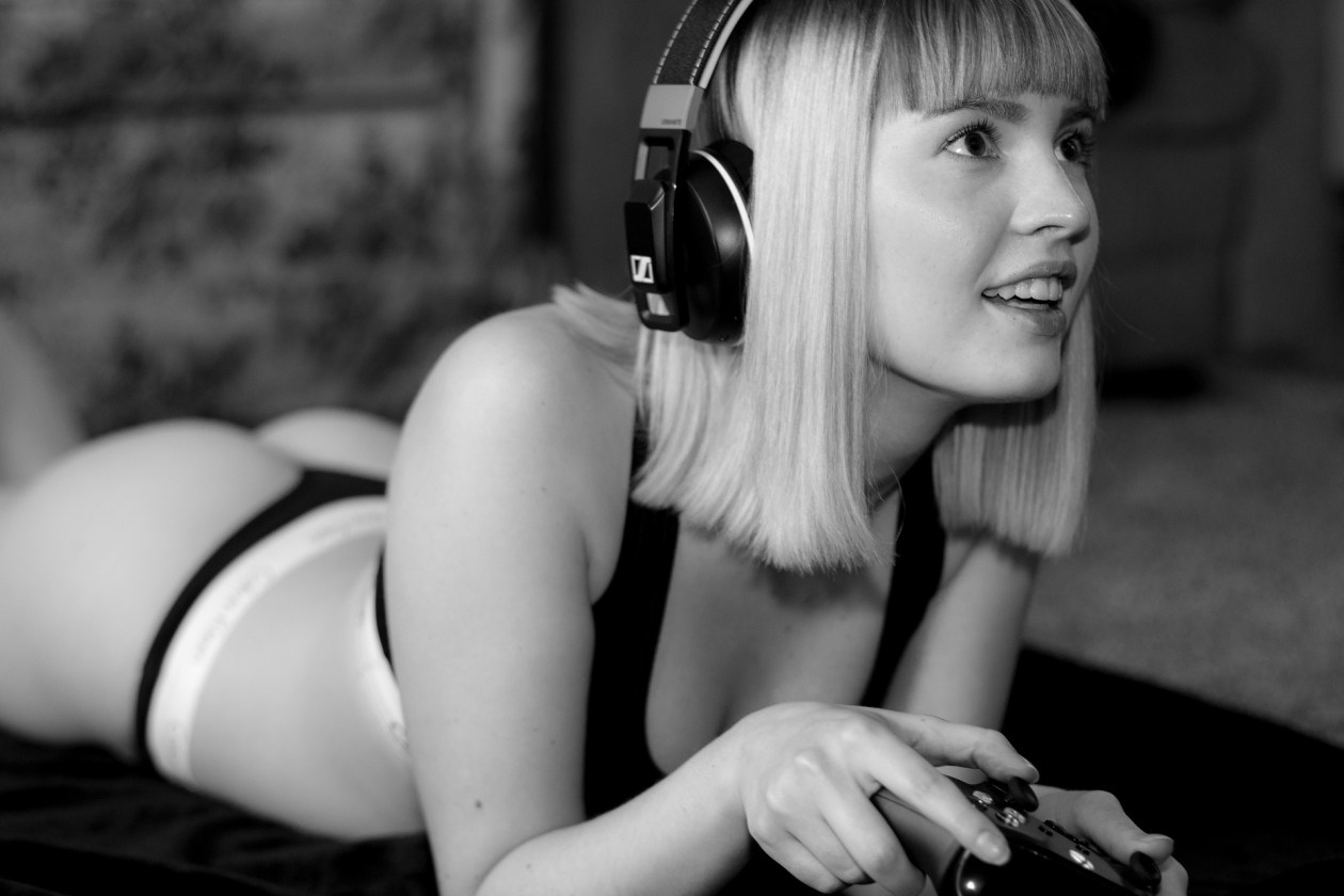 Girl wearing headphones lying naked holding a video games console. Photo.