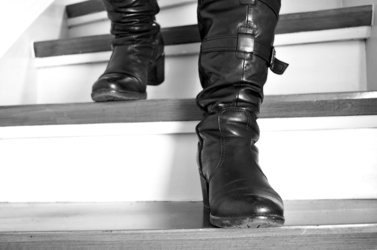 Black leather knee-high boots desending stairs. Photo.