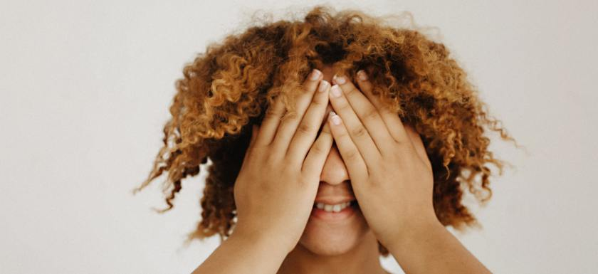 A woman with a short afro covering her eyes in embarrassment while smiling. Photo.