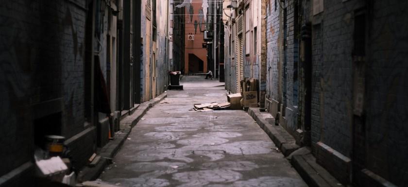 Narrow ally way between tall buildings. Photo.