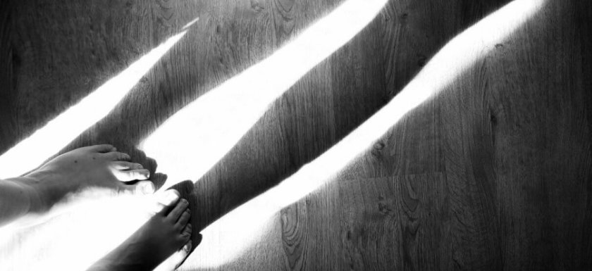 Shadows of legs fall across the black-and-white wooden floor. Photo.