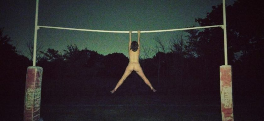 A naked woman hanging by her arms from a set of rugby goal posts. Photo.