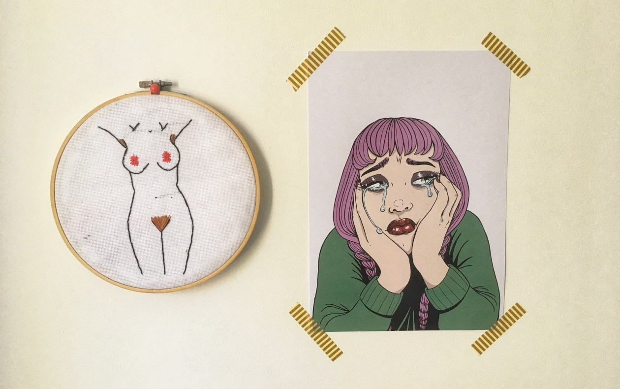 A cross stitch of a naked body with pubic and underarm hair and a drawing of a sad girl with purple hair are pinned to the wall. Photo.