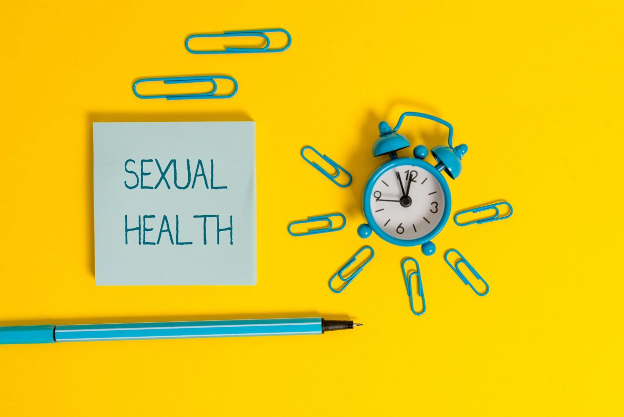 A post it note reading 'sexual health' lies on a yellow background with a metal alarm clock and matching paperclips. Photo.