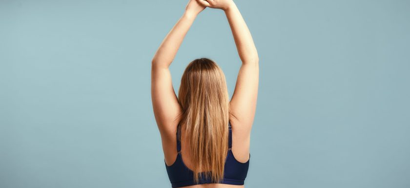 Back view of a woman with beautiful long hair raising hands up while standing against blue wall. Photo.