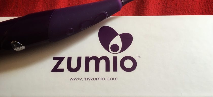 A purple silicone sex toy tapering to a small head sits on a white box that reads 'Zumio' on red sheets. Photo.
