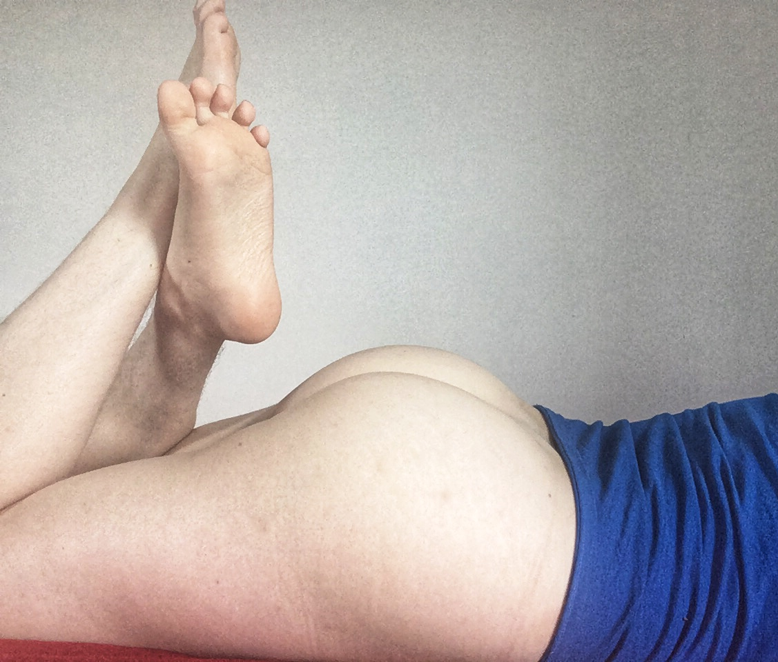 An afab person wearing a blue shirt is naked from the waist down and lying on their front with their legs kicked up, emphasising their naked ass. Photo.