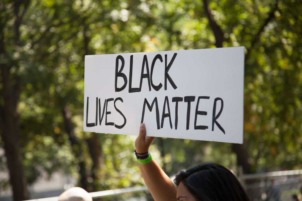A protestor holding up a 'black lives matter' sign. Photo.