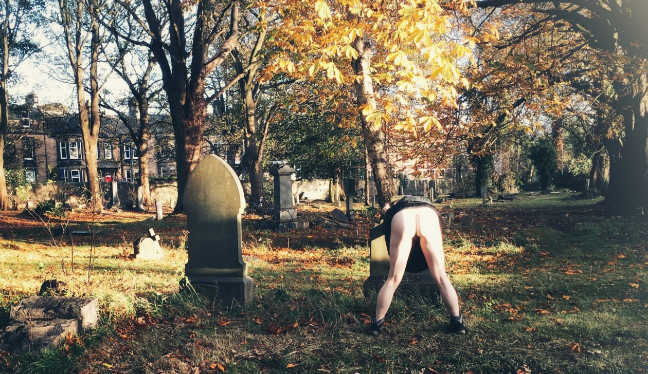An afab person bends over a gravestone, lifting their skirt to show their bare arse. They are next to another, taller, gravestone in an autumn sunlit graveyard covered in yellow leaves. Photo.