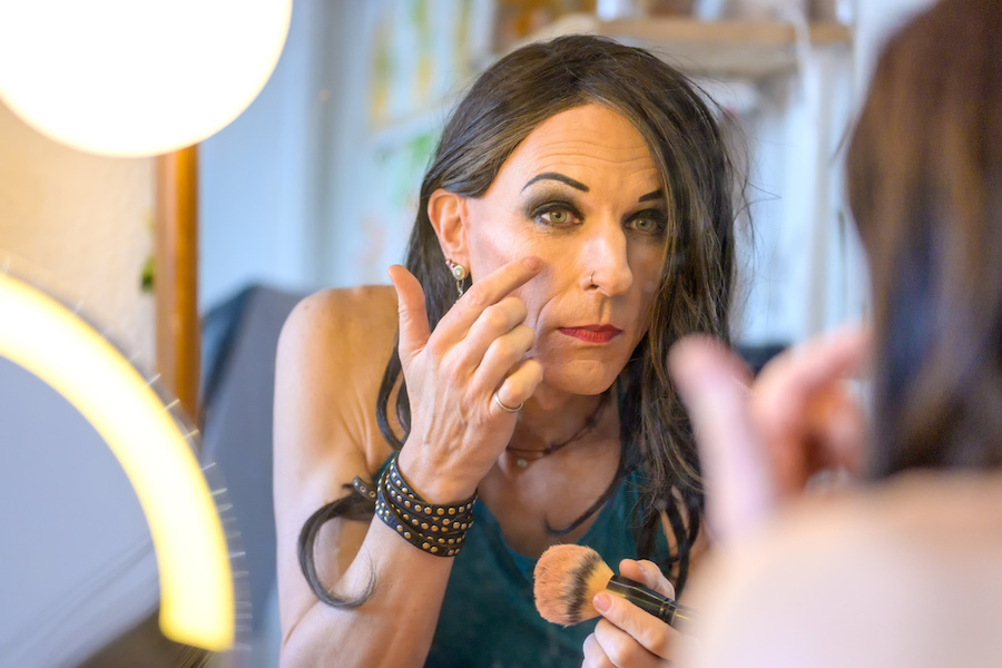 A trans woman leans forward to apply her make up. Photo.