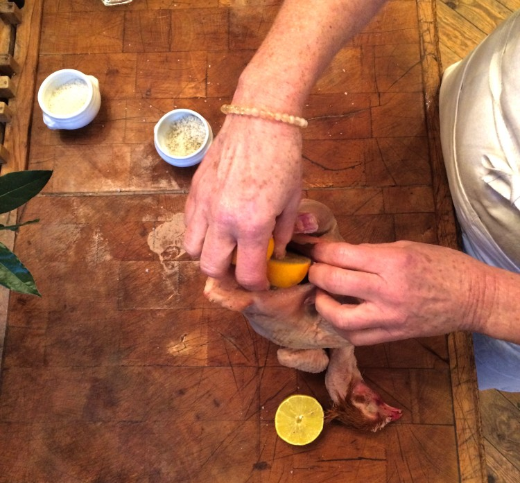 Adding the lemon, cut in half, to the cavity, then adding the giblets.