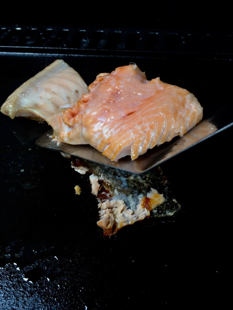When the grill is hot, place the salmon on the plancha (you can also place it right on the grill), skin-side down.  Put the butter in a heat proof pan and place it on the grill as well.  Close the grill and cook the salmon until it is translucent through, which should take 8 minutes.  Check the salmon; if it is just about but not quite entirely cooked, you can leave it on the grill another minute or two, remembering that it will continue to cook even when you remove it from the grill.